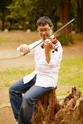 切り株に腰掛けてヴァイオリンを演奏している・いちろーたの写真