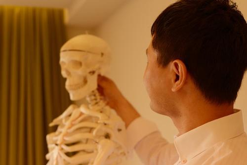 骨格模型ヘンリーくんの首を触りつつ見つめるいちろーた